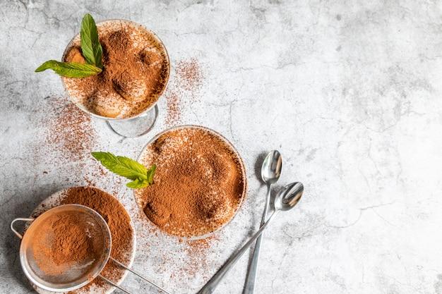 Tiramisú de postre italiano tradicional en un frasco de vidrio con cacao y menta en gris