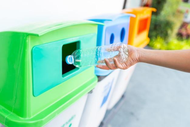 Tirar una botella de agua de plástico en la papelera de reciclaje
