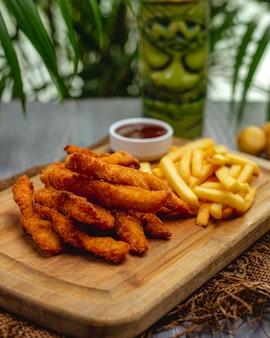 Tiras de pechuga de pollo empanadas fritas con salsa de tomate y papas fritas en una tabla de madera
