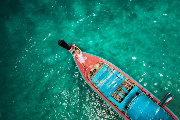 Tiro aéreo del abejón de una mujer rubia joven en un vestido rosado y gafas de sol en el frente de un barco tailandés del longtail de madera. aguas cristalinas y corales en una isla tropical y una playa increíble.