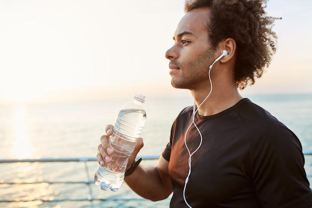 Tiro al aire libre de elegante atleta masculino de piel oscura bebiendo agua de una botella de plástico después del entrenamiento cardiovascular. runner hidratando durante el entrenamiento junto al mar bajo el sol de la mañana.
