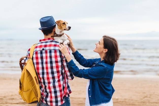 Tiro al aire libre de la familia amigable y su perro favorito llegan al mar