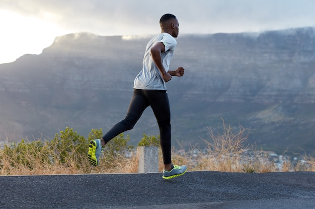 Tiro al aire libre de joven atlético viste camiseta informal, pantalones y zapatillas de deporte, posa contra la montaña, está lleno de energía, copia espacio para su contenido publicitario o promoción.