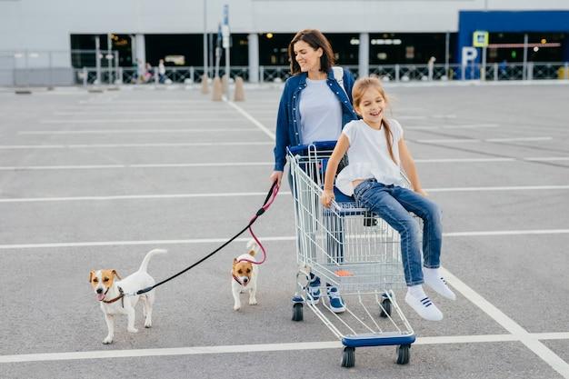 Tiro al aire libre de la madre feliz y su pequeña hija caminar con perros con correa