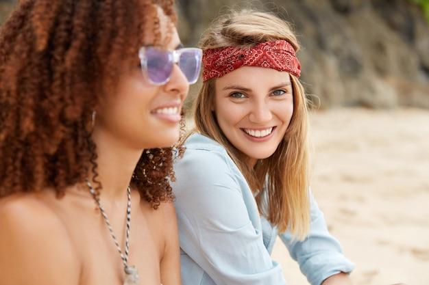 Tiro al aire libre de mujeres lesbianas felices que se recrean juntas en la playa de arena, tienen expresiones positivas, discuten el destino futuro. alegre mujer afroamericana tiene buen descanso con novia europea