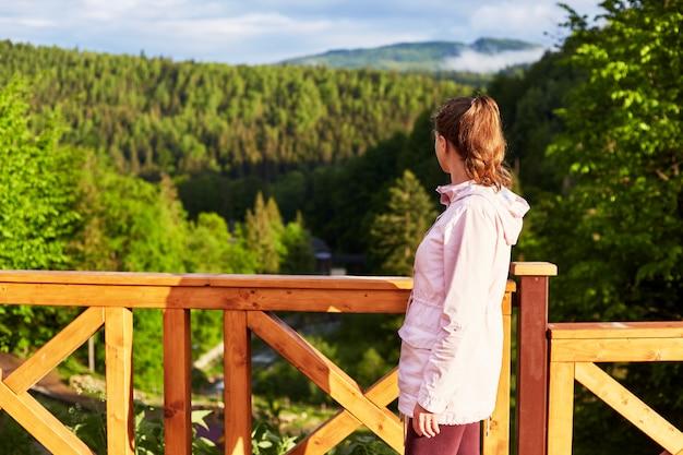 Tiro al aire libre del puente de madera o balcón al lado de la montaña, bosque verde y colinas soleadas, perfil de joven delgada mujer de pie
