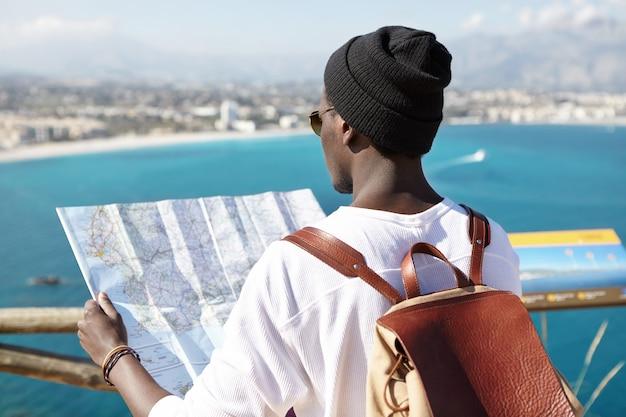 Tiro al aire libre del turista de piel oscura con mochila de cuero en los hombros con una guía de papel en las manos, frente a la hermosa vista de la costa del mar europeo, de pie en la plataforma de turismo