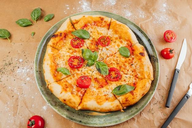 Tiro de alto ángulo de una deliciosa pizza con rodajas de tomate y hojas de albahaca