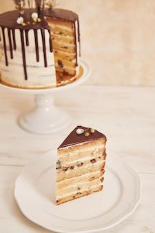 Tiro de alto ángulo de delicioso pastel boho con goteo de chocolate y flores con adornos dorados
