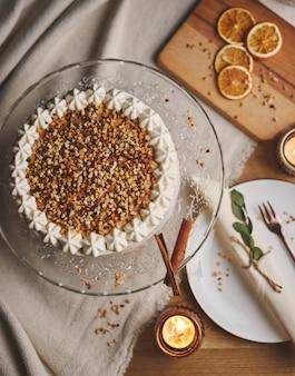 Tiro de alto ángulo de un delicioso pastel de navidad blanco con nueces y mandarina