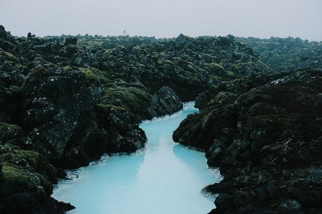 Tiro de alto ángulo de un hermoso río sinuoso que fluye a través de las rocas cubiertas de musgo