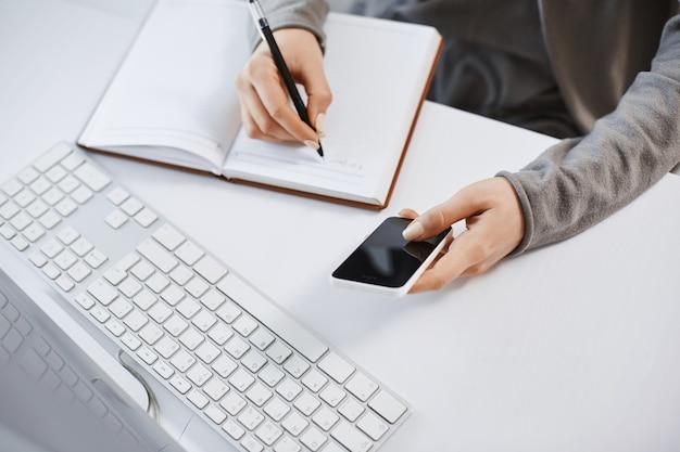 Tiro de alto ángulo de manos de mujer trabajando con gadgets. captura recortada del teléfono inteligente femenino moderno que sostiene mientras escribe el plan en el cuaderno, sentado cerca del teclado y la computadora, teniendo dificultades en la oficina