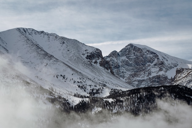 Tiro de alto ángulo de las montañas cubiertas de nieve bajo el cielo nublado
