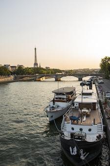 Tiro de alto ángulo de un yate atracado en el río con la torre eiffel