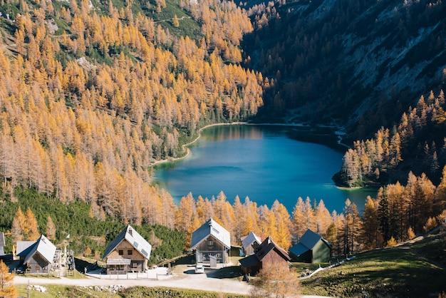 Tiro alto de un pequeño lago entre montañas con un pequeño pueblo cerca de la base de la montaña