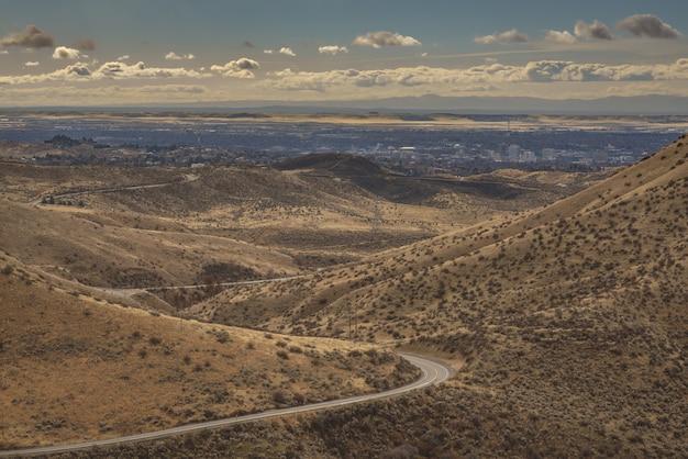 Tiro de ángulo alto de una carretera con curvas en medio de las montañas con edificios de la ciudad en la distancia