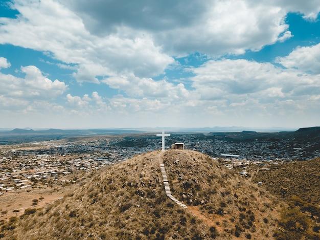 Tiro de ángulo alto de colinas cubiertas de hierba seca con una gran cruz blanca en la parte superior bajo un cielo azul