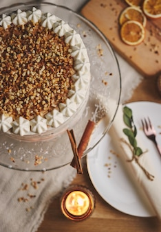 Tiro de ángulo alto de un delicioso pastel blanco con nueces y mandarina
