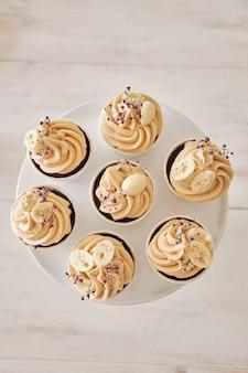 Tiro de ángulo alto de deliciosos cupcakes de chocolate con cobertura de crema blanca