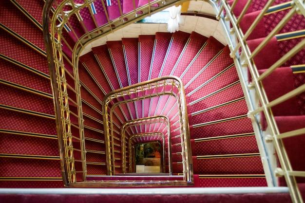 Tiro de ángulo alto de una escalera de caracol rosa con manijas doradas en un hermoso edificio