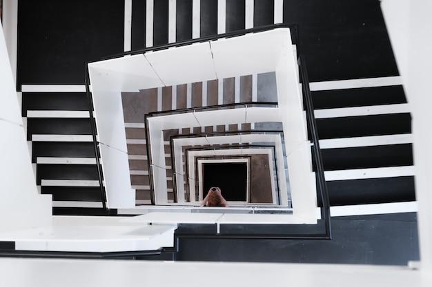 Tiro de ángulo alto de escaleras de caracol y una mujer tomando una foto durante el día
