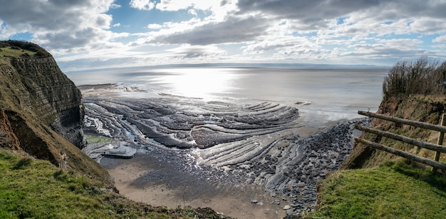 Tiro de ángulo alto de una hermosa orilla del mar bajo las colinas y el cielo nublado en el fondo