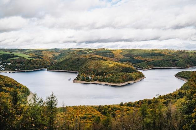 Tiro de ángulo alto de un hermoso lago rodeado de colinas en otoño bajo el cielo nublado