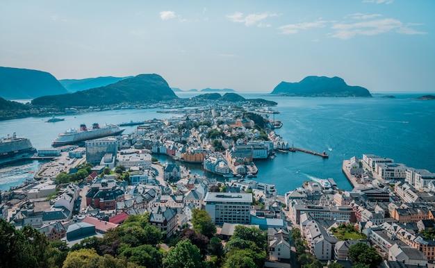 Tiro de ángulo alto de muchos edificios en la orilla del mar cerca de altas montañas en noruega