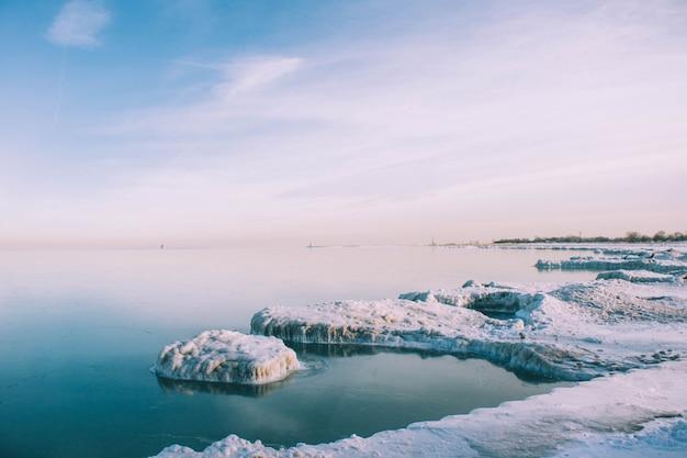 Tiro de ángulo alto de la orilla congelada del mar en invierno bajo el cielo tranquilo
