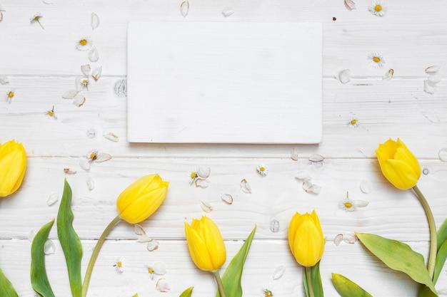 Tiro de ángulo alto de un papel en blanco con tulipanes amarillos sobre una mesa blanca
