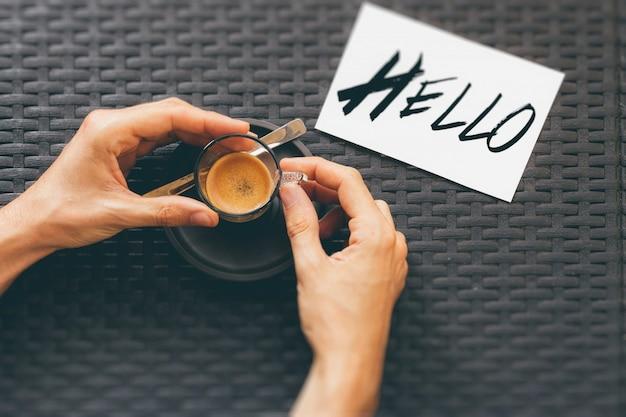 Tiro de ángulo alto de una persona que bebe una taza de café cerca de una impresión hola en una tarjeta blanca