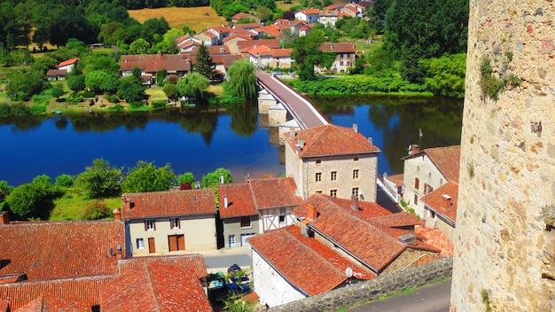 Tiro de ángulo alto de un puente y edificios con techo rojo a lo largo de un río