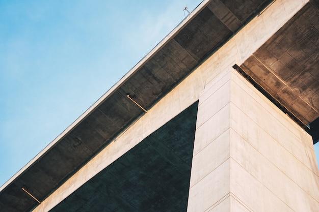 Tiro de ángulo bajo de un alto puente de piedra con cielo azul claro