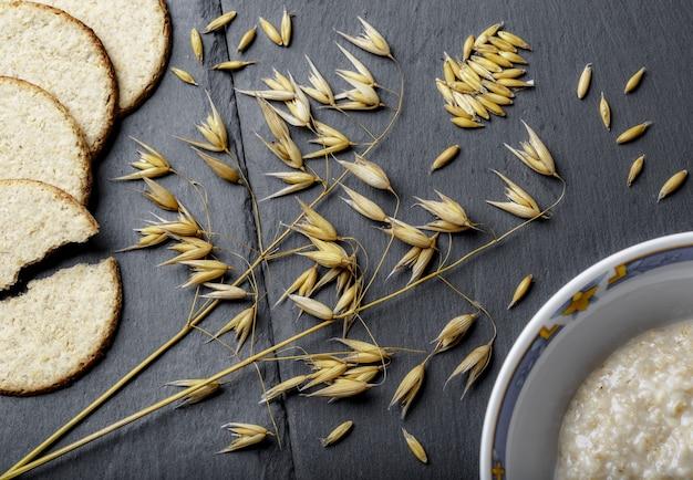Tiro de ángulo alto de ramas de trigo, pan fresco y gachas de avena sobre una superficie gris