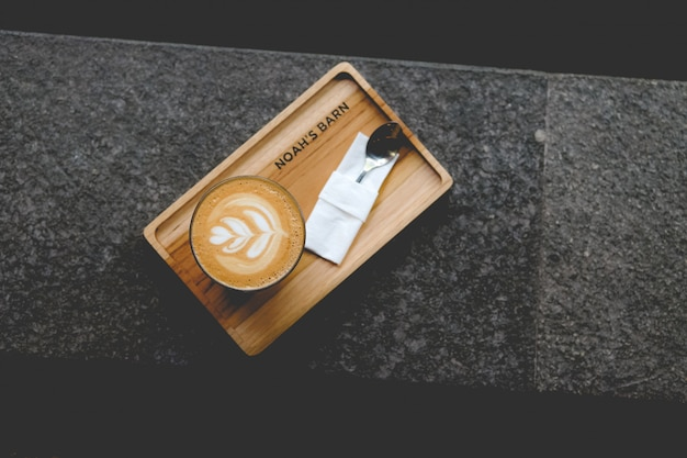 Tiro de ángulo alto de una taza de arte latte en una bandeja de madera