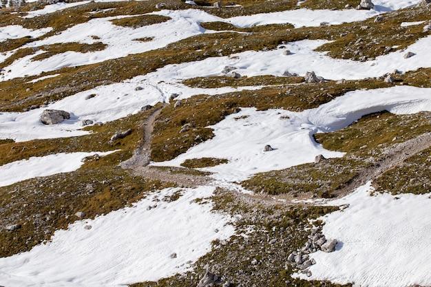 Tiro de ángulo alto de texturas de tierra parcialmente cubiertas de nieve en los alpes italianos