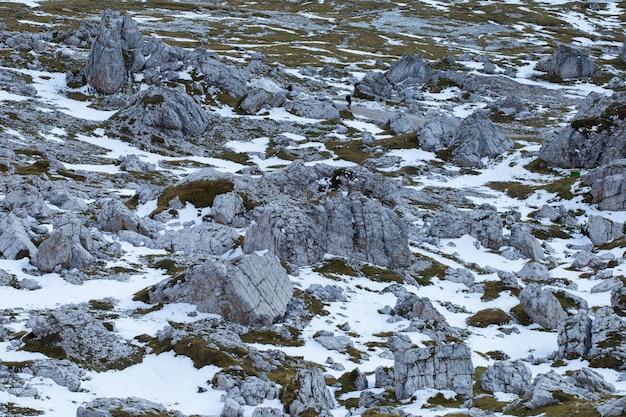 Tiro de ángulo alto de texturas de tierra pedregosa cubiertas de nieve en los alpes italianos