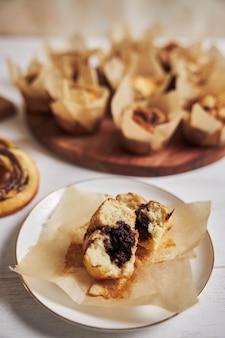 Tiro de ángulo alto vertical de un delicioso muffin de chocolate cerca de algunos muffins y donas en una mesa