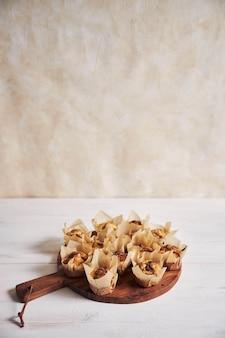 Tiro de ángulo alto vertical de delicioso muffin de chocolate en una placa de madera sobre una mesa blanca