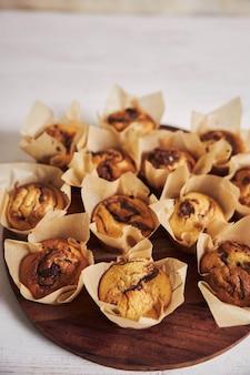 Tiro de ángulo alto vertical de deliciosos muffins de chocolate en una placa de madera sobre una mesa blanca