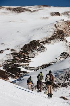 Tiro de ángulo alto vertical de excursionistas con mochilas en las montañas nevadas