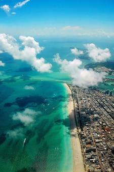 Tiro de ángulo alto vertical de un hermoso paisaje urbano junto al mar bajo un cielo nublado