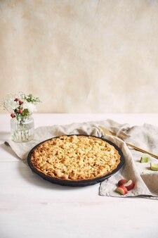 Tiro de ángulo alto vertical de un plato de tarta de tarta rhabarbar crujiente y algunos ingredientes sobre una mesa