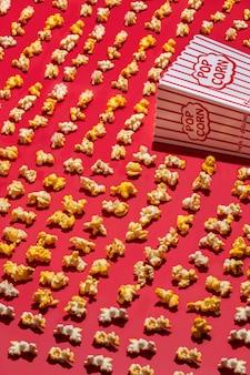 Tiro de ángulo alto vertical de una taza de palomitas de maíz de papel y palomitas de maíz esparcidas sobre una superficie roja