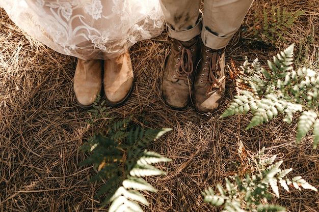 Tiro de ángulo alto de los zapatos viejos de la novia y el novio de pie sobre la hierba seca