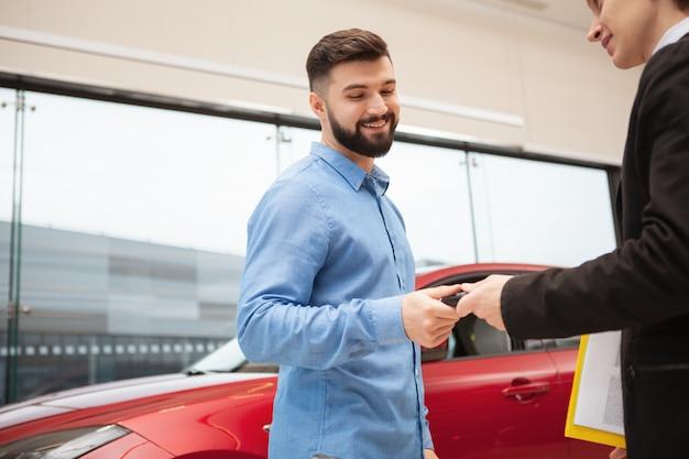 Tiro de ángulo bajo de un apuesto hombre barbudo que recibe las llaves de su nuevo coche en el concesionario de automóviles