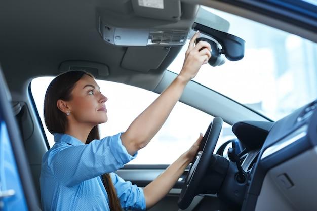 Tiro de ángulo bajo de una atractiva mujer ajustando un espejo mientras está sentado en un automóvil
