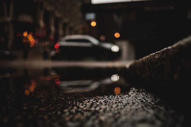 Un tiro de ángulo bajo de un automóvil con reflejo en el charco de agua