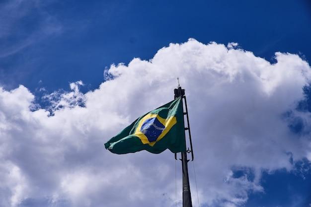 Tiro de ángulo bajo de la bandera de brasil bajo las hermosas nubes en el cielo azul