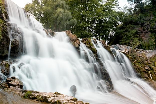 Tiro de ángulo bajo de una cascada rocosa con árboles verdes en el fondo